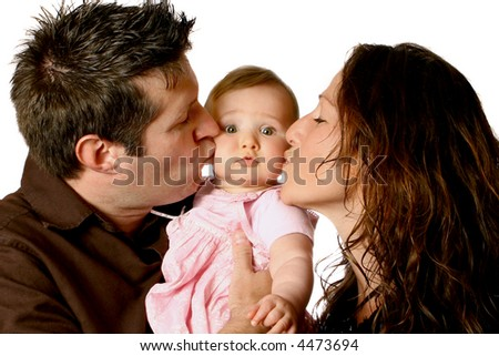 Dotting mom and dad kissing beautiful baby girl in pink dress. - stock photo