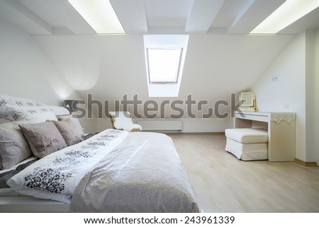 Double and comfortable bed in bright bedroom - stock photo