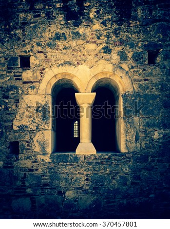 Double arched window on a facade of medieval wall. Biforium - ancient window with column, old architecture element of Roman and Gothic styles. - stock photo