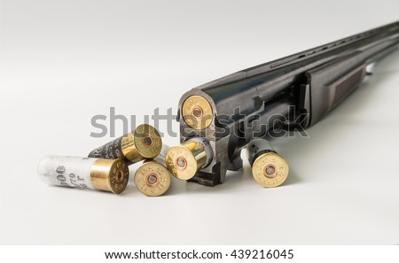 double-barreled hunting gun with cartridges on a light background.