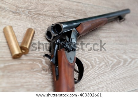 double-barreled hunting rifle closeup on wooden background - stock photo