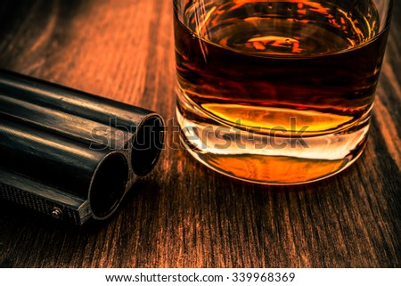 Double-barreled shotgun barrel and glass of whiskey close-up. Focus on the barrel, image vignetting and the orange-blue toning