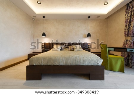 Double bed in brown colored modern bedroom interior
