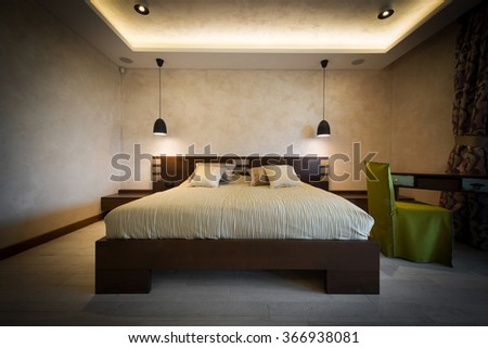 Double bed in brown colored modern bedroom interior - stock photo