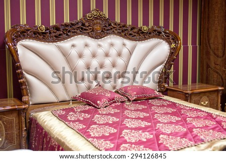 Double bed with decorative headboard. - stock photo