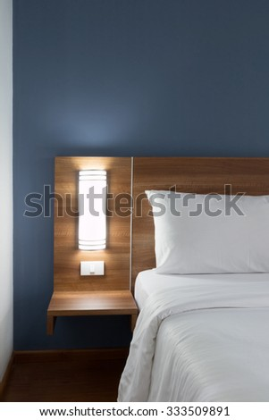 Double bed with wood headboard.
