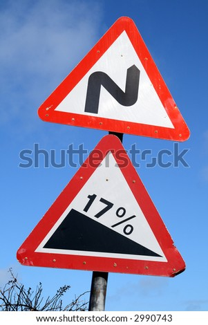 Double bend and steep hill British road warning signs. - stock photo