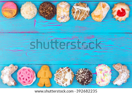 Double border of colorful cookies or biscuits arranged in a line on a turquoise blue crackle paint wooden background, overhead view with copy space - stock photo