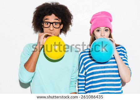 Double bubble love. Funky young couple inflating balloons while standing against white background  - stock photo