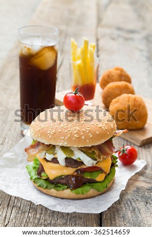 Double burger with fries in ketchup, fried balls and coca cola - stock photo