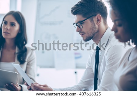 Double checking the contract. Young handsome man reading document while sitting at office with his beautiful coworkers  - stock photo