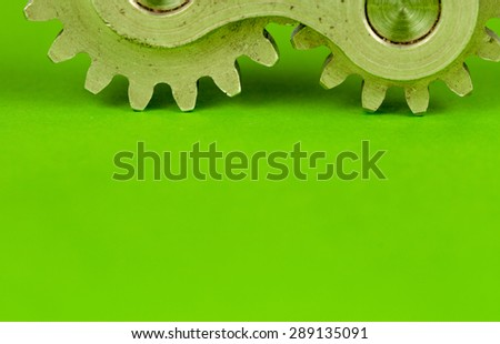 Double cogwheels mechanical machinery element on green planar background surface, showing light touching concept of metal shine cogs that are meant to spin, not stand, but probably move occasionally - stock photo