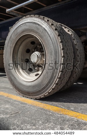 Double construction truck wheel side perspective close up angled weathered and worn rubber tyre