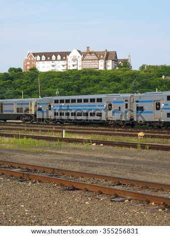 double  decker commuter train on tracks under historic manor hotel on hill Montauk Hamptons Long Island New York Usa