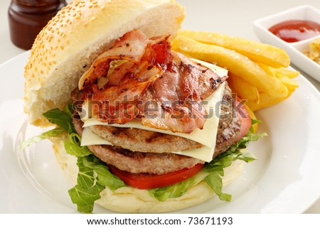 Double decker hamburger with bacon and cheese ready to serve. - stock photo