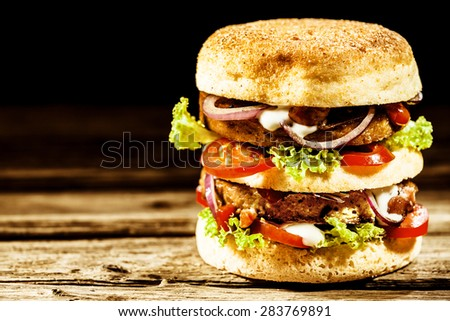 Double-decker, or club, freekeh burger with assorted fresh salad trimmings on a golden bread roll served on a rustic wooden table with copyspace - stock photo