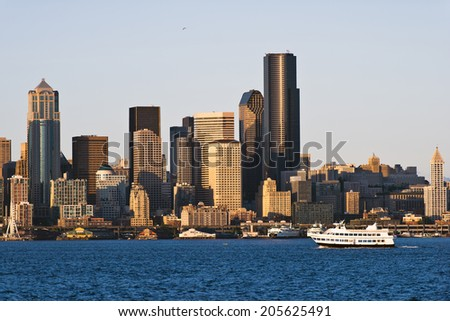 Double-decker passenger boat in the bay on the Pacific coast of Seattle on a background of a large number of skyscrapers, multi-storey offices, classical and modern buildings in Down Town. - stock photo
