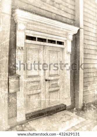 Double door entrance to a wooden tree house with a carved ornament portal, textured in vintage sepia tones.  - stock photo