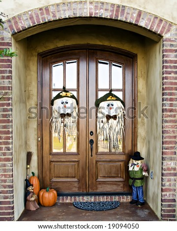 Double Doors decorated with scarecrow faces and other fall decorations. - stock photo