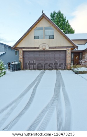 Double doors garage winter time with tire tracks on the long driveway - stock photo