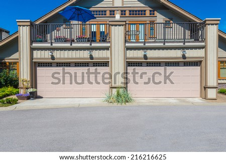 Double doors garage with nicely paved driveway. - stock photo