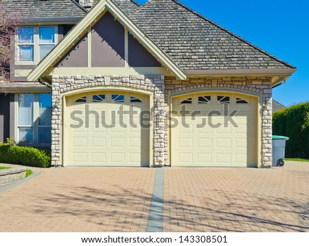 Double doors garage with nicely paved driveway. Canada. - stock photo