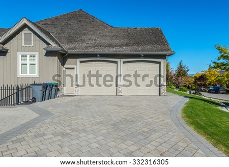 Double doors garage with nicely paved driveway. North America. - stock photo