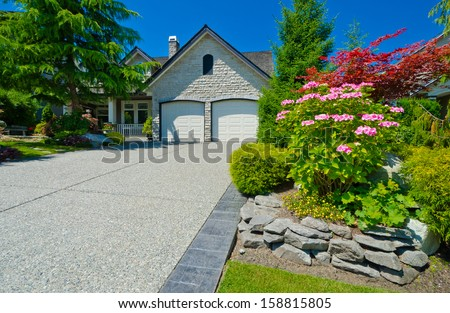 Double doors garage with wide and long driveway with nicely trimmed and landscaped front yard. North America. Vertical. - stock photo