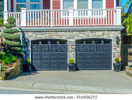 Double doors garage with wide, long driveway.