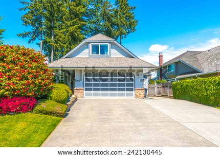 Double doors garage with wide long driveway. North America. - stock photo
