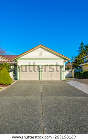 Double doors garage with wide, long driveway. North America. Canada. Vertical.
