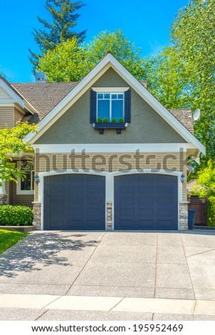 Double doors garage with wide long driveway. Vertical. - stock photo