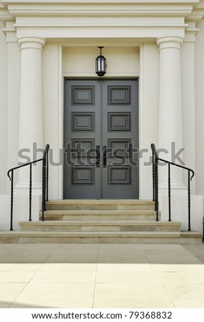 Double doors with rectangular inset patterns stand at the top of steps. There are handrails bordering the steps leading to the doors. Vertical shot. - stock photo