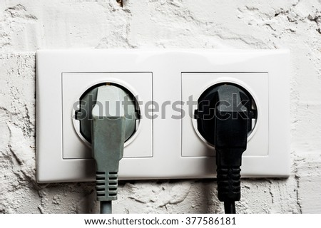 Double electrical socket with plugged cables on brick wall, macro shot - stock photo