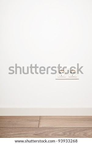 Double electricity power socket (European standard) on blank white wall background over moder wooden floor - stock photo