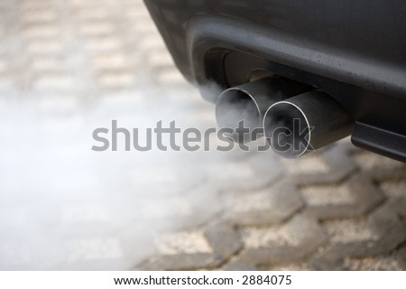 Double exhaust pipe of a car - blowing out the pollution. - stock photo