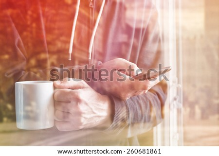Double exposure Adult Man Drinking Coffee And Texting with Mobile Phone in Morning by the Window. Selective Focus with Shallow Depth of Field. - stock photo