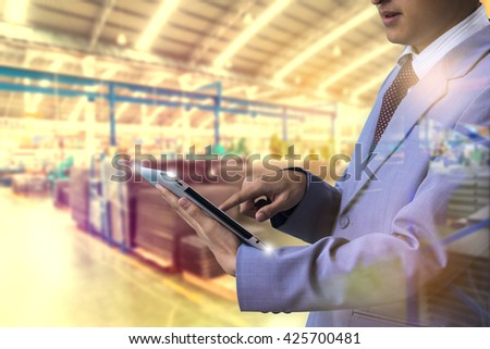 Double exposure authorities Quality Inspector use tablet inspecting a small manufactured part and factory with blur background Factory Plant bulbs - stock photo