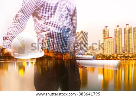 Double exposure ,builder engineer holding security helmet look at blueprint paper construction drawing plan with city twilight background. - stock photo