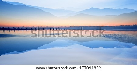 Double exposure effect of mountains and sunrise beach landscape - stock photo