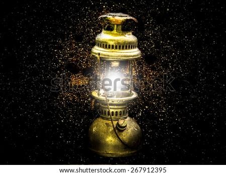 Double exposure gold lamp on dark background - stock photo