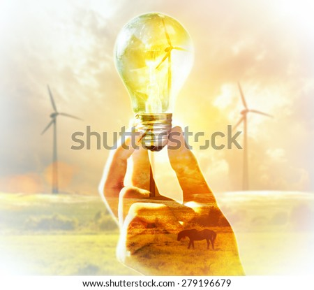 Double exposure. Hand holding light bulb on a wind turbine background. Environment, eco technology and energy concept. - stock photo