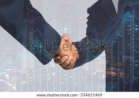 Double exposure handshake between businessman on cityscape and financial graph background, Business Trading concept - stock photo