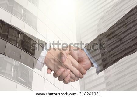 double exposure handshake between businessman on Modern glass building background - stock photo