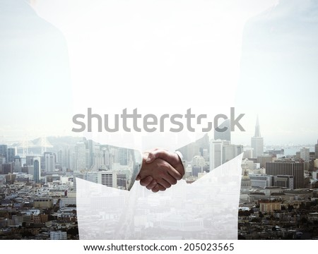 double exposure handshake businessman on city background - stock photo