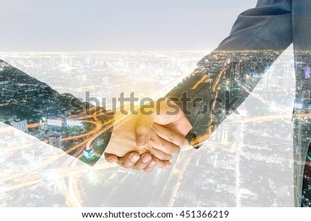 Double exposure handshake of business peoples on the colorful night city background, Concept for business teamwork and success. - stock photo