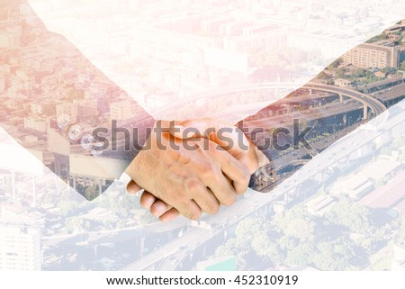 Double exposure handshake of business peoples on the top view of cityscape background.   - stock photo