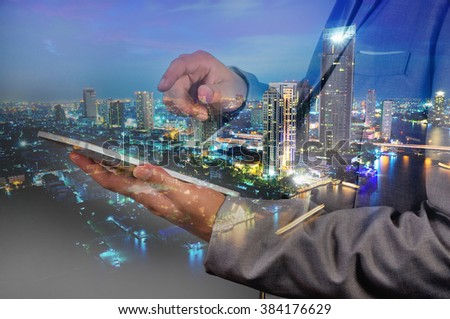 Double Exposure image of Businessman use Digital Tablet and City Building at Twilight