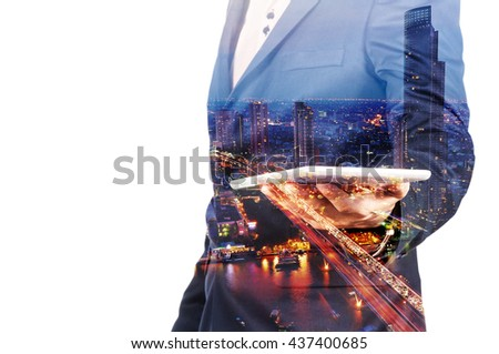 Double Exposure image of Businessman use Digital Tablet and City Building at Twilight as Business Technology concept