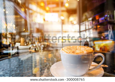 double exposure latte coffee made with warm Vintage Tones, blur coffee shop background  - stock photo